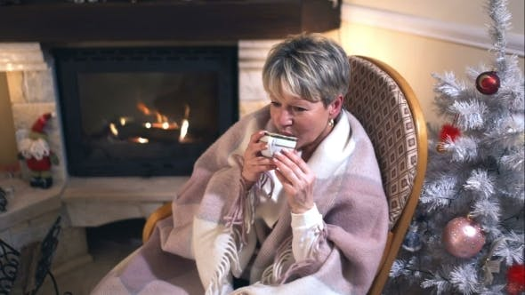 Mature Woman Drinking Coffee In a Cozy Living Room