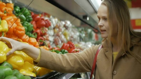 Thumbnail for Happy Girl Buying Fresh Yellow Peppers In Grocery