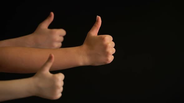 Thumbnail for Raising Hands with Thumbs Up on Black Background.