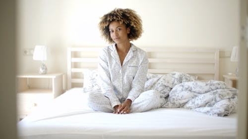 Woman In Pajamas Sitting On Bed