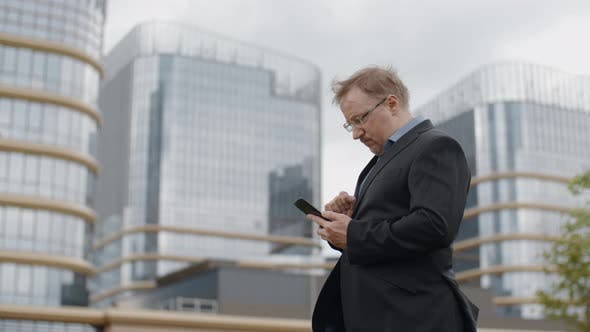 Cover Image for Funny Man in Suit Texting on Smartphone, Adult Manager Using Mobile Device Outside Office Building