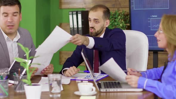 Bearded Team Leader in Business Suit Having a Meeting with His Investment Team