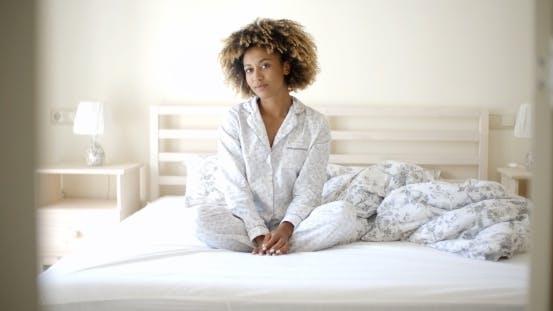 Frau im Pyjamas sitzend auf Bett