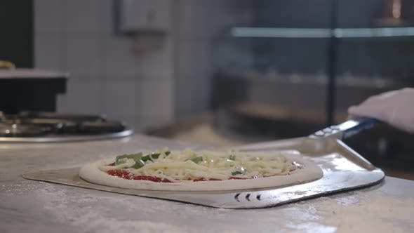 Thumbnail for Closeup of Raw Pizza on Cooking Shovel in Restaurant Kitchen