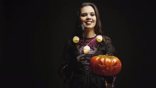 Lächelnde Hexe hält Kürbis über schwarzem Hintergrund