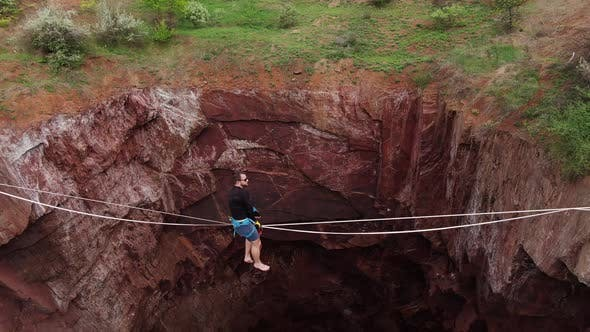 Scary Pit Under a Man Who Is Sitting on a Slackline Massive Pit