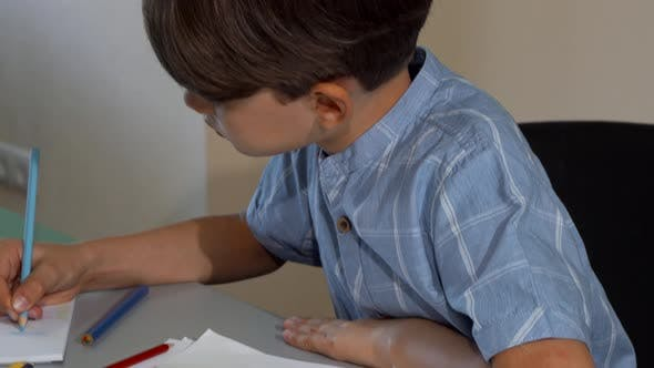 Cute Little Boy Smiling To the Camera While Drawing