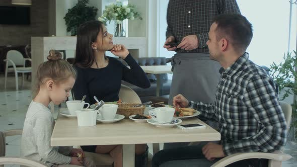 Thumbnail for Happy Mother, Father and Little Girl Having Dinner Asked Waiter To Take Picture By Smartphone.