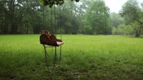 Thumbnail for Leere Holzschaukel schwankend langsam im Regen