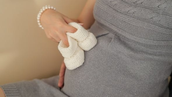 Thumbnail for Pregnant Woman Holding Little Shoes