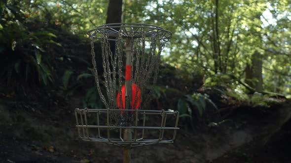 Thumbnail for Orange Frisbee Disc Slow Motion In Forest Golf Basket