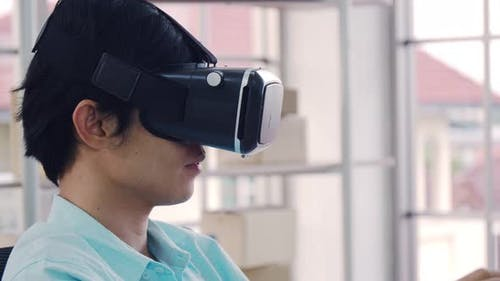 Asian man wearing virtual reality glasses experiencing innovative technology.