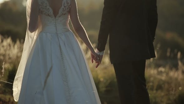 Thumbnail for Young Bride And Groom At Sunset Holding Hands