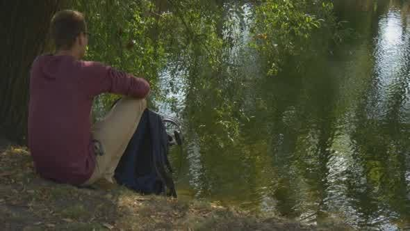 Thumbnail for Man With Backpack Comes to River Bank Sits to The