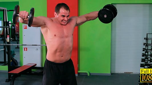 Thumbnail for A Man Raises His Arms With Dumbbells