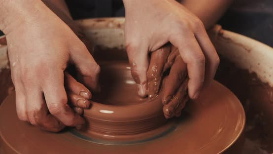 Thumbnail for The Hands of a Man and a Woman in Clay on a Potter's Wheel Mold a Vase