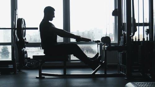 Der Kerl macht Übungen auf dem Übungsgerät