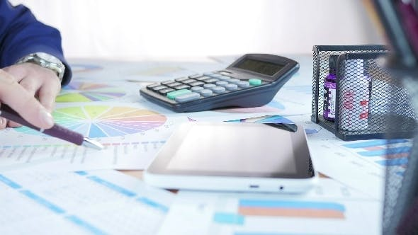 Businessman Analyzing Diagram And Calculation