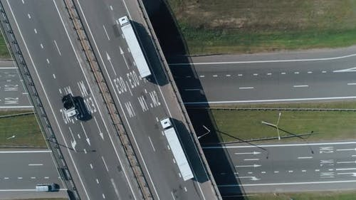 Convoy of Trucks Ride on the Highway Bridge, Road Junction Near Forest, Logistic Transportation