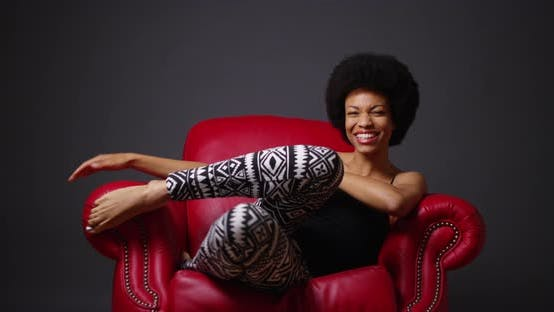 Thumbnail for Black woman sitting in red leather armchair