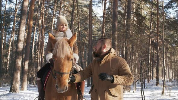 Thumbnail for Man and Woman Enjoying Horseback Riding in Winter Forest