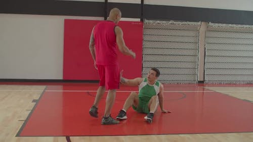 Basketball Player Helping Opponent To Stand Up