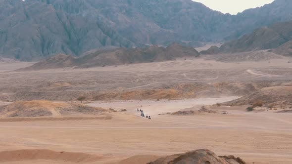 Column of a Quad Bike Rides Through the Desert in Egypt on Backdrop of Mountains. Driving ATVs. - product preview 0