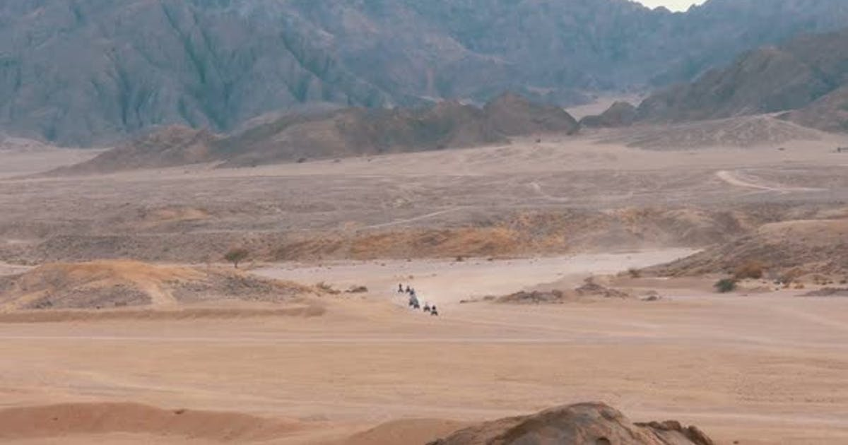 Column of a Quad Bike Rides Through the Desert in Egypt on Backdrop of Mountains. Driving ATVs.