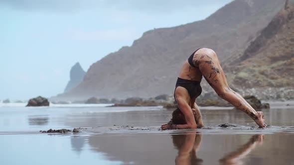 Thumbnail for A Beautiful Woman in a Swimsuit Performs a Headstand on a Beach with Black Sand Near the Sea
