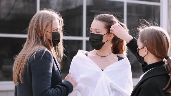 Thumbnail for Drei hübsche Freundinnen setzen Schutzmasken auf.