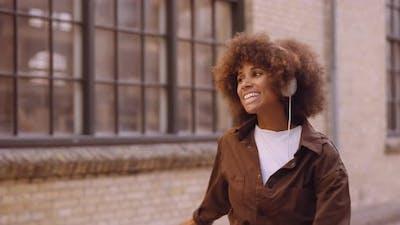 Woman Dancing On Street To Music Through Headphones