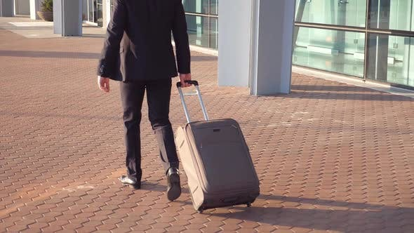 Rear View of Unrecognizable Young Businessman in a Suit Walking Near Terminal and Pulling Suitcase