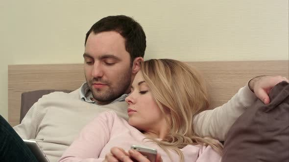 Thumbnail for Young Couple Lying in Bed, Man Using Digital Tablet, Bored Woman Using Smartphone