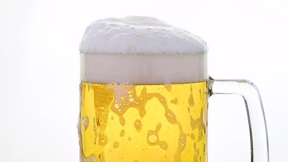 Pouring Lager Beer in Glass Over White