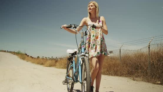 Thumbnail for Young woman walking with bike