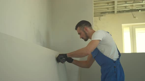 Repairman Makes Notes on the Wall with a Pencil