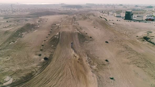 Aerial view of man practicing circuit motocross at desert landscape, U.A.E.
