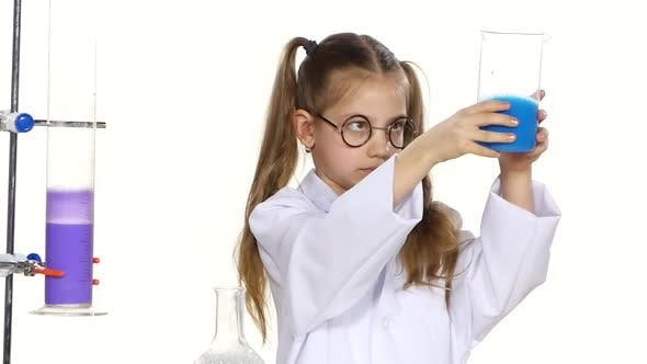 Thumbnail for Cute Girl with Ponytails in Uniform and Round Glasses Evaluates Chemical Experiments on White