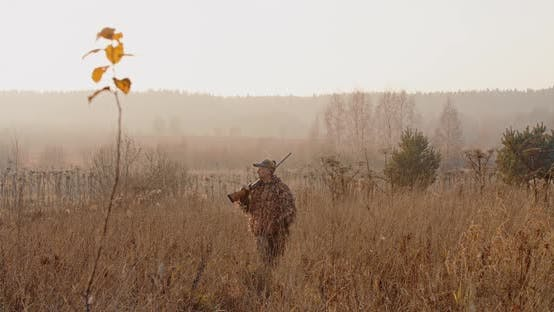 Thumbnail for Hunter With Rifle on His Shoulder Walks Through the Field at Foggy Morning