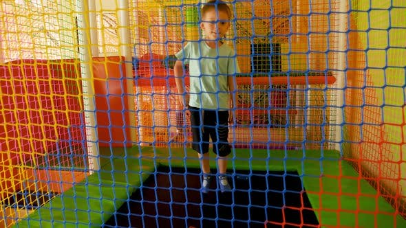 Slow Motion of Cheerful Little Boy Jumping on Trampoline and Playing on Playground