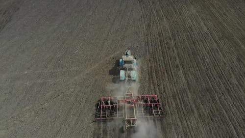A Tractor with a Harrow Cultivates the Land