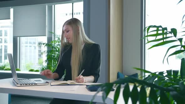 Thumbnail for Elegant Woman Working in Stylish Office. Modern Blond Woman in Trendy Suit Sitting at Table in Light