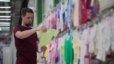 Man is Viewing and Touching Baby Suits in Store