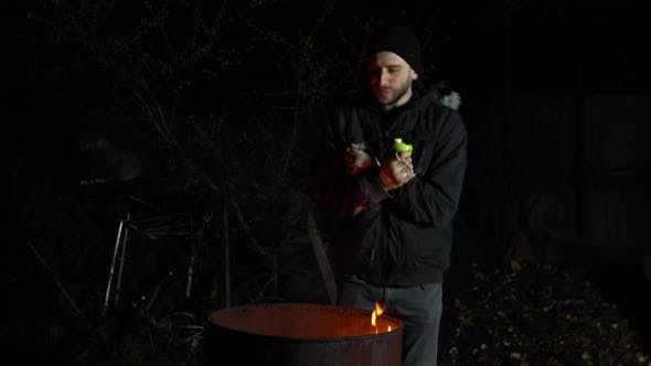 Thumbnail for A Homeless Young Man Stands By the Fire and Eats an Apple. A Man Stands at Night Near a Barrel of