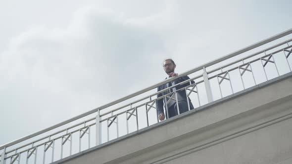 Wide Shot of Depressed Caucasian Businessman in Eyeglasses Approaching To Bridge Fence. Portrait of