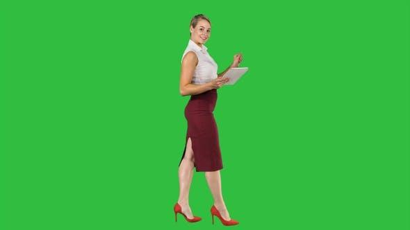 Thumbnail for Woman walking using digital tablet and talking to camera