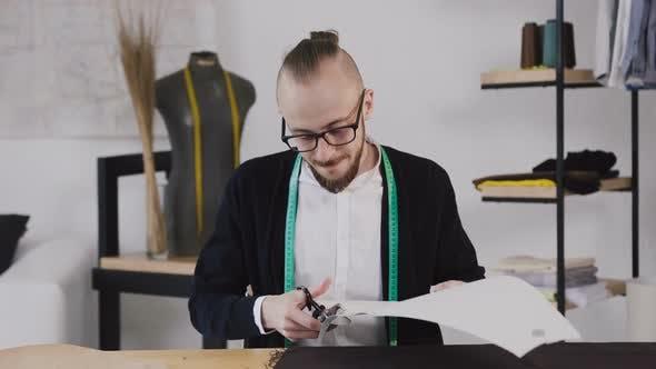 Thumbnail for Junge Designer oder Schneider sitzen an einem Arbeits Nähtisch im Studio