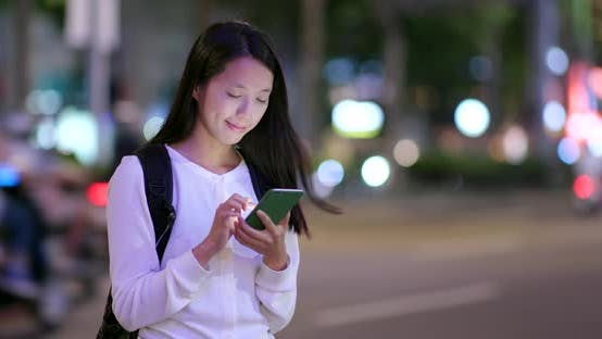 Thumbnail for Woman use of smart phone in the city at night
