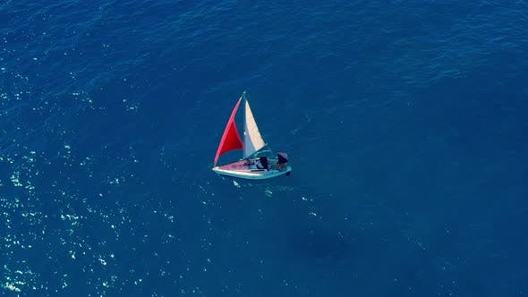 Thumbnail for Aerial View. Sailing Yacht with Red Sail in the Open Sea