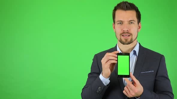 Thumbnail for A Young Businessman Talks To the Camera and Holds Out a Smartphone with Green Screen